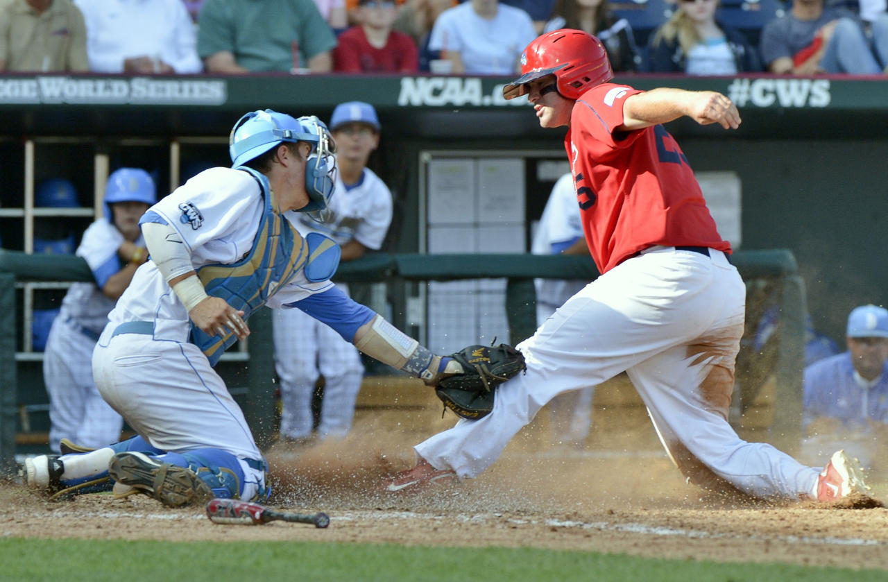 Stony Brook's Kevin Courtney, right, is tagged out at home plate by UCLA catcher Tyler Heineman on a double play hit into by Stony Brook batter Travis Jankowski in the fifth inning of an NCAA College World Series baseball game in Omaha, Neb., Friday, June 15, 2012. (AP Photo/Ted Kirk)