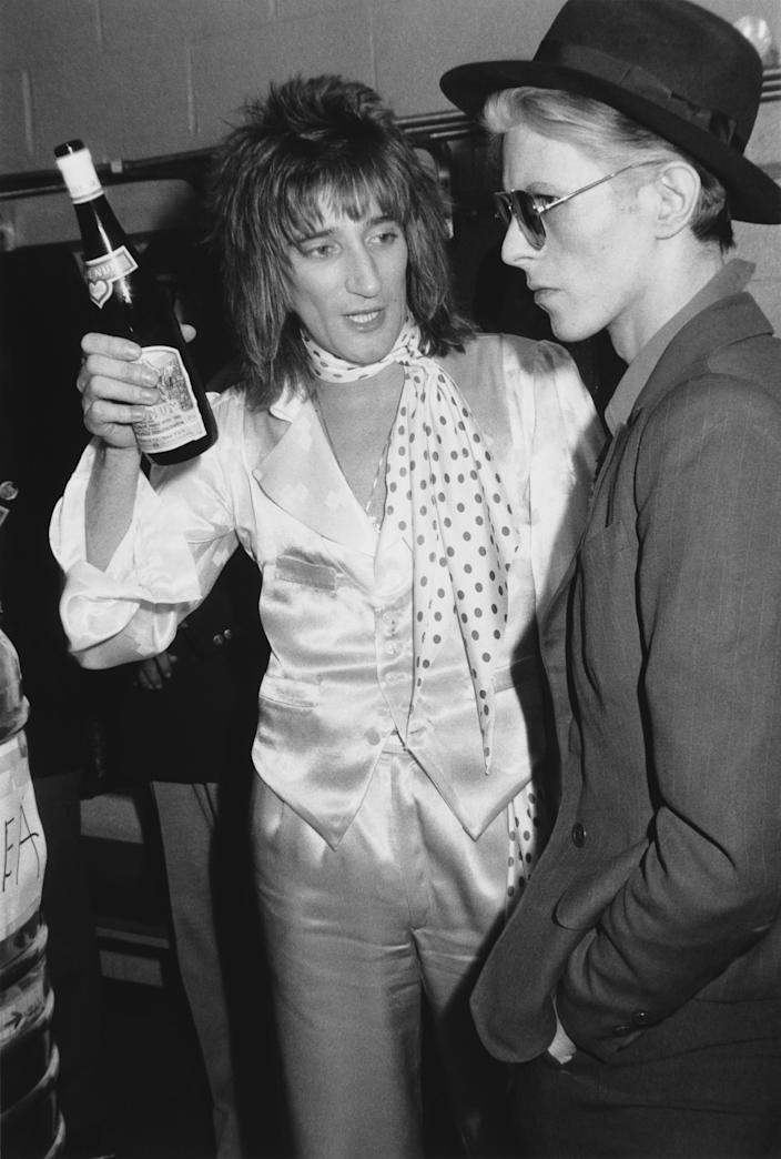 24th February 1975:  British singer Rod Stewart holds a bottle of Blue Nun wine and talks with British singer David Bowie backstage at Madison Square Garden, where Stewart performed, New York City. Stewart is wearing matching satin pants and vest, with a satin shirt and polka-dot scarf. Bowie is wearing a suit with a fedora hat and aviator sunglasses.  (Photo by Hulton Archive/Getty Images)