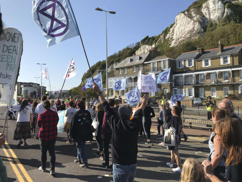 "Extinction Rebellion protesters occupy one side of a dual carriageway at the port of Dover, England, Saturday Sept. 21, 2019. Traffic around the Port of Dover, England's major sea connection with France, has been disrupted as a result of a protest by environmental activists. Activists from Extinction Rebellion said their protest around the port is intended to ""highlight the vulnerability of the U.K.'s food supply in the face of the ecological and climate emergency."" (Michael Drummond/PA via AP)"