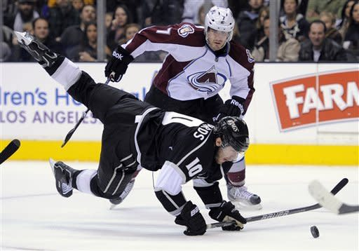 Los Angeles Kings center Mike Richards, below trips as he passes the puck as Colorado Avalanche right wing David Van der Gulik looks on during the second period of their NHL hockey game, Saturday, Jan. 21, 2012, in Los Angeles. (AP Photo/Mark J. Terrill)