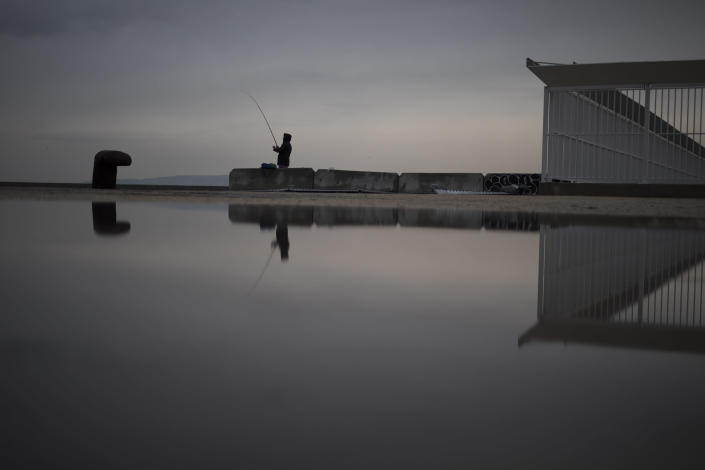 FILE - In this Jan. 10, 2021 file photo, a fisherman reels in his line before a curfew is enforced in Marseille, southern France. Trying to fend off the need for a third nationwide lockdown that would further dent Europe's second-largest economy and put more jobs in danger, France is instead opting for creeping curfews. (AP Photo/Daniel Cole, File)