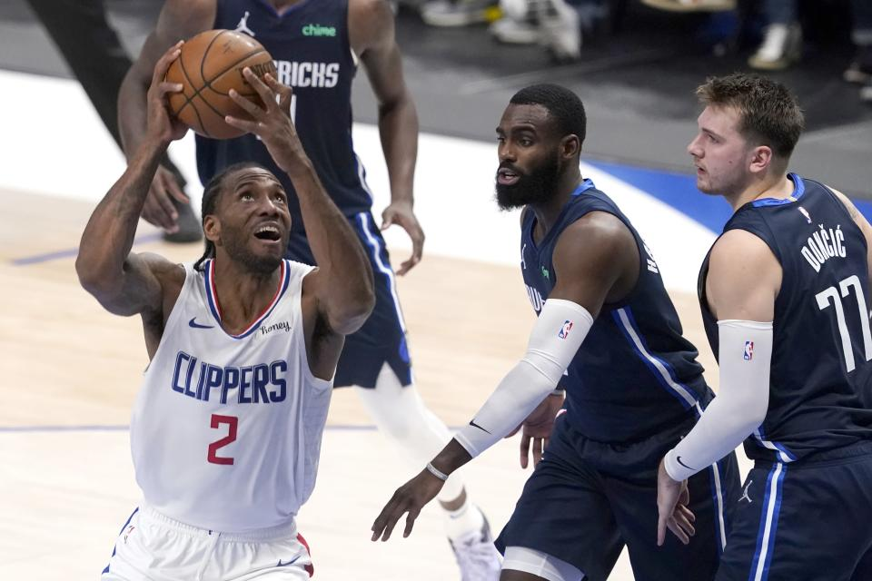 Los Angeles Clippers forward Kawhi Leonard (2) positions for a shot as Dallas Mavericks' Tim Hardaway Jr., center, and Luka Doncic (77) defend in the first half in Game 3 of an NBA basketball first-round playoff series in Dallas, Friday, May 28, 2021. (AP Photo/Tony Gutierrez)