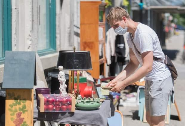 The province of Saskatchewan is telling buyers and sellers to stay home if they are unwell and physically distance while at garage or yard sales.  (Graham Hughes/The Canadian Press - image credit)