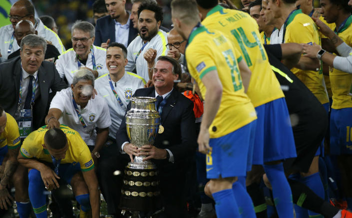 Brazil's President Jair Bolsonaro poses with players celebrating with the trophy after a 3-1 victory over Peru in the final soccer match of the Copa America at the Maracana stadium in Rio de Janeiro, Brazil, Sunday, July 7, 2019.(AP Photo/Silvia Izquierdo)