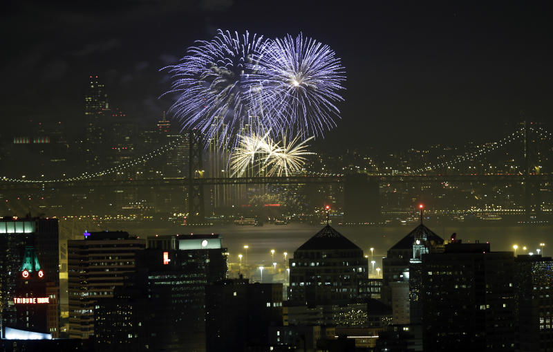 Fireworks fill the air in the bay over the Oakland, bottom, and San Francisco skylines, divided by the San Francisco Oakland Bay Bridge, as part of New Year's Eve celebrations in a view from Oakland, Calif. on Wednesday, Jan. 1, 2014. (AP Photo/Marcio Jose Sanchez)