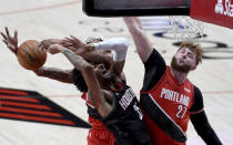 Houston Rockets forward Christian Wood, left, drives to the basket on Portland Trail Blazers center Jusuf Nurkic, right, during the first half of an NBA basketball game in Portland, Ore., Saturday, Dec. 26, 2020. (AP Photo/Steve Dykes)