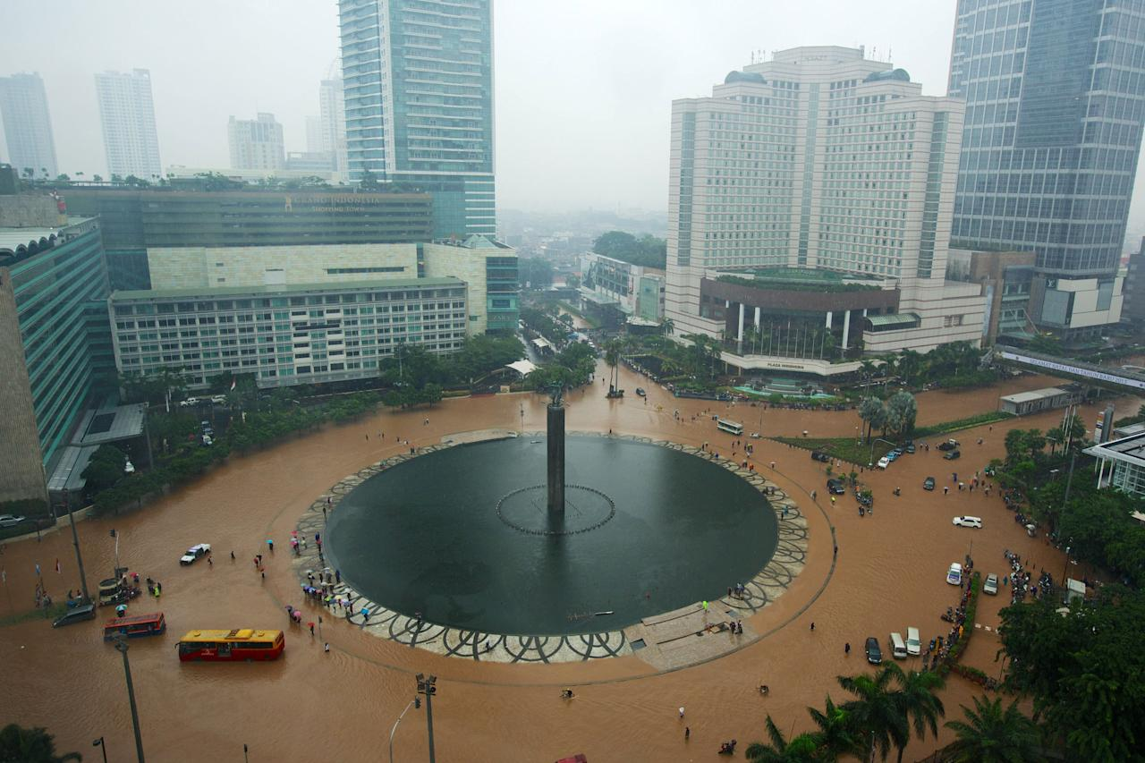 JAKARTA, INDONESIA - JANUARY 17:  People struggle through floodwaters in Jakarta's central business district on January 17, 2013 in Jakarta, Indonesia.  Thousands of Indonesians were displaced and the capital was covered in many key areas in over a meter of water after days of heavy rain. (Photo by Ed Wray/Getty Images)