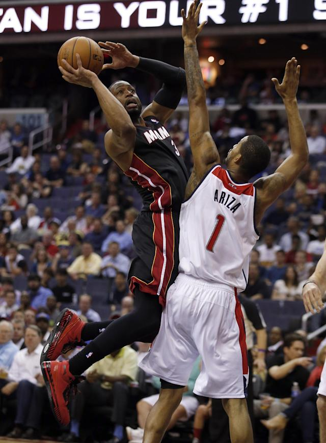 Miami Heat guard Dwyane Wade (3) shoots over Washington Wizards forward Trevor Ariza (1) in the first half of an NBA basketball game, Monday, April 14, 2014, in Washington. (AP Photo/Alex Brandon)