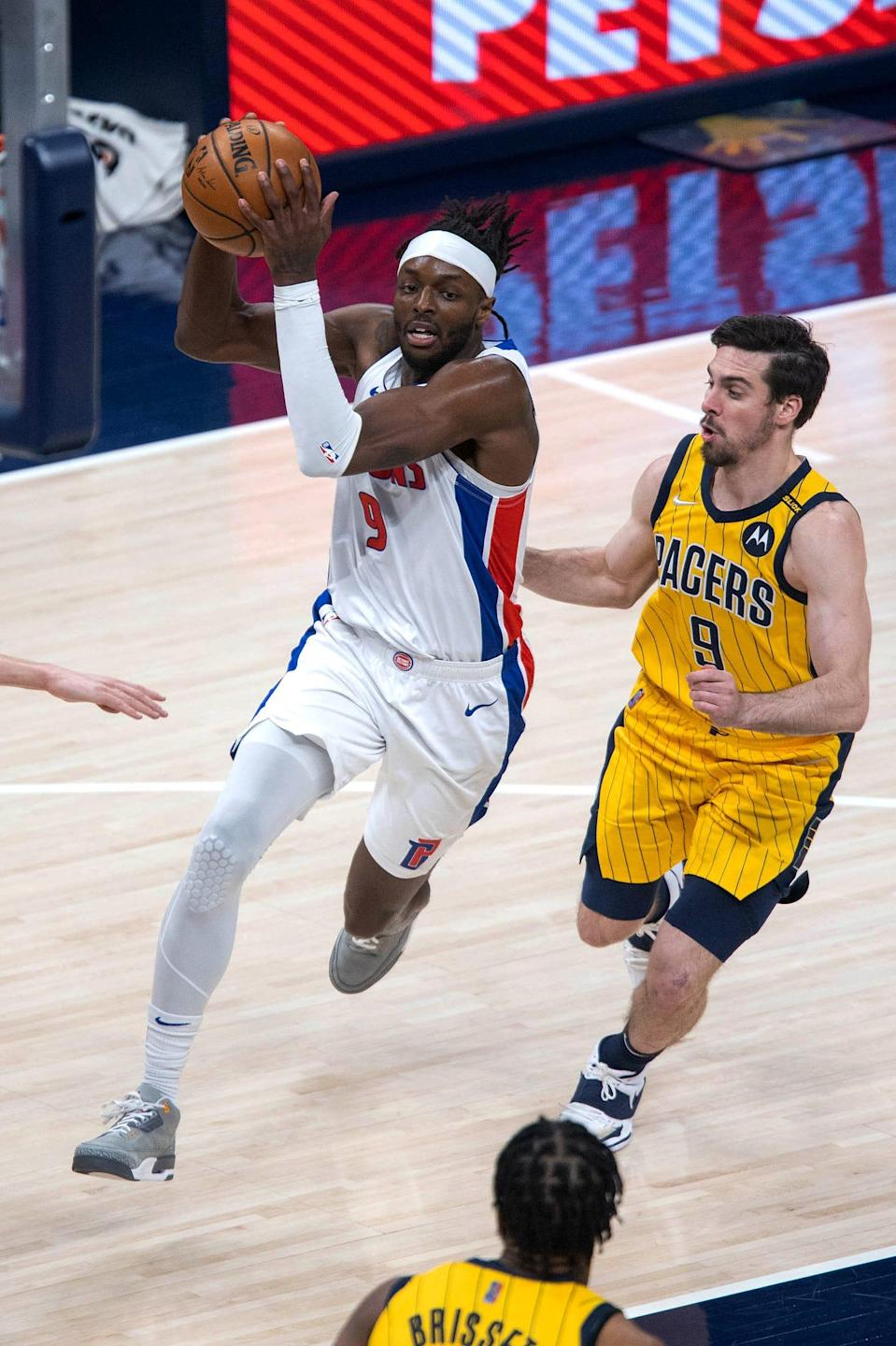 Pistons forward Jerami Grant dribbles the ball against Pacers guard T.J. McConnell in the third quarter on Saturday, April 24, 2021, in Indianapolis.