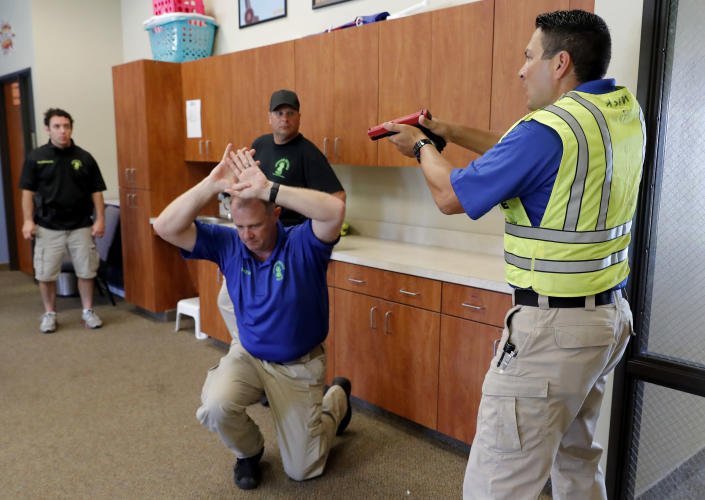 In this July 21, 2019 photo, Police officers David Riggall, kneeling, and Nick Guadarrama, right, instruct students Bryan Hetherington, left rear, and Chris Scott, center rear, during a security training session at Fellowship of the Parks campus in Haslet, Texas. While recent mass shootings occurred at a retail store in El Paso, Texas, and a downtown entertainment district in Dayton, Ohio, they were still felt in houses of worship, which haven't been immune to such attacks. And some churches have started protecting themselves with guns. (AP Photo/Tony Gutierrez)
