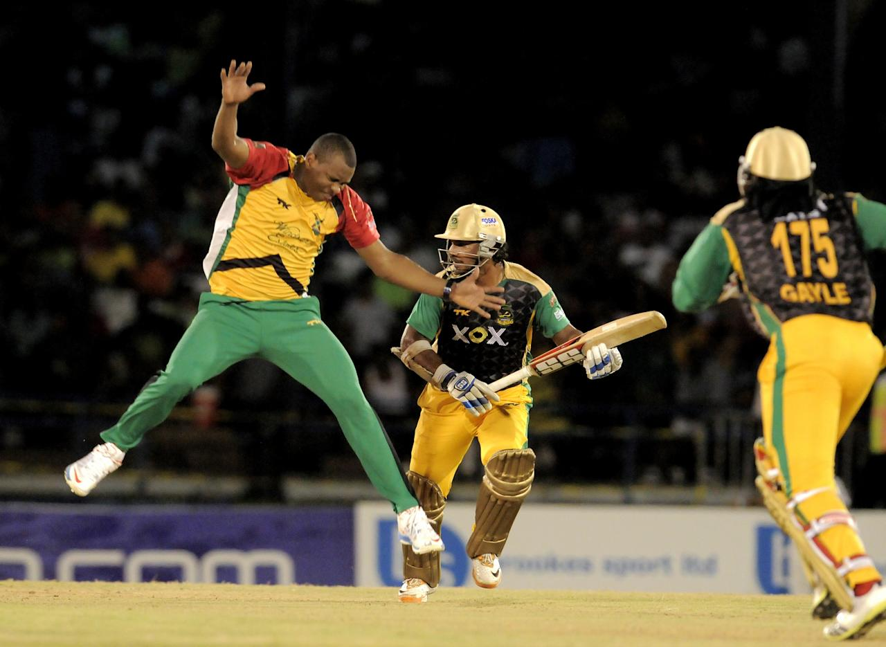 PORT OF SPAIN, TRINIDAD AND TOBAGO - AUGUST 24:  Christopher Barnwell of Guyana Amazon Warriors attempts to stop Jamaica Tallawahs Chris Gayle during the Final of the Caribbean Premier League between Guyana Amazon Warriors v Jamaica Tallawahs at Queens Park Oval on August 24, 2013 in Port of Spain, Trinidad and Tobago. (Photo by Randy Brooks/Getty Images Latin America for CPL)