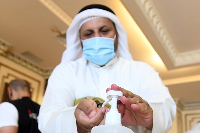 KUWAIT CITY, KUWAIT - JUNE 10: Mask-clad Muslim worshippers sanitises his hand after pulling a disposable prayer mat before heading to perform the noon prayers at the Bilal bin Rabah Mosque for the first time since a lockdown was instated three months prior due to the novel coronavirus (COVID-19) pandemic in Kuwait City, Kuwait on June 10, 2020. (Photo by Jaber Abdulkhaleg/Anadolu Agency via Getty Images)