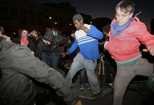 <p>Protesters from Occupy Oakland knock down fences to escape from the police after they were surrounded to be detained on a vacant lot in Oakland on January 28. Riot police fired tear gas and arrested more than 400 people in Oakland, California, as hordes of anti-Wall Street protesters tried to take over downtown buildings including City Hall, police said</p>
