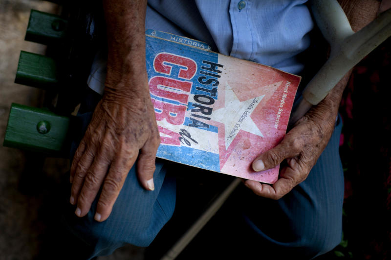 In this picture taken Aug 1, 2012, Rafael Vega, 84, holds the paperback cover of a Cuban history book that he uses to fan himself, at a senior center, that provides retirees with medical attention, meals and social activities, in Havana, Cuba. Cuba grapples with having the oldest citizenry in Latin America, a phenomenon fueled by low birth rates and long life expectancies, plus the migration of young people and women. The government has already postponed the retirement age and is trying to create more homes and programs for the elderly, but still will have to handle the economic consequences of its increasingly graying population.(AP Photo/Ramon Espinosa)