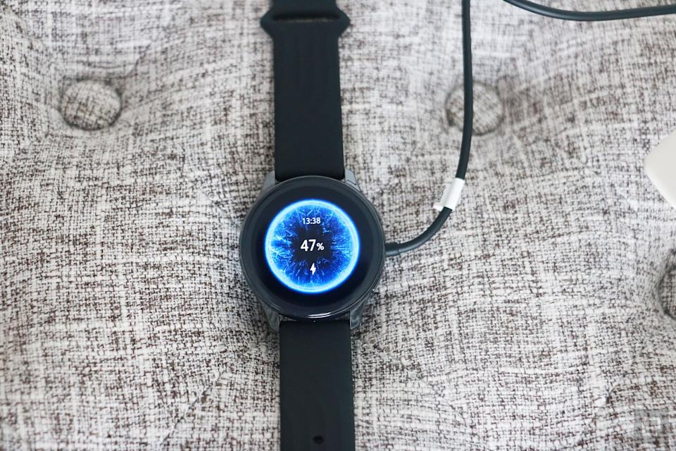 OnePlus Watch review photos. OnePlus Watch on a charger with display showing 47 percent battery and time at 1:38pm.