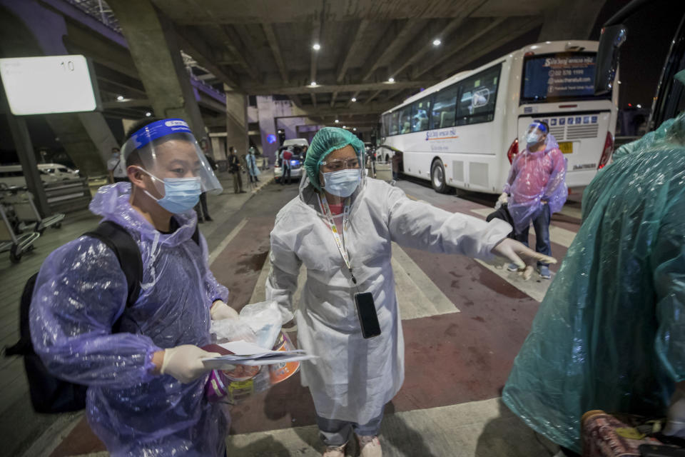 A public health worker guides Chinese tourists from Shanghai who arrived at Suvarnabhumi airport on special tourist visas, in Bangkok, Thailand, Tuesday, Oct. 20, 2020. Thailand on Tuesday took a modest step toward reviving its coronavirus-battered tourist industry by welcoming 39 visitors who flew in from Shanghai, the first such arrival since normal traveler arrivals were banned almost seven months ago. (AP Photo/Wason Wanichakorn)
