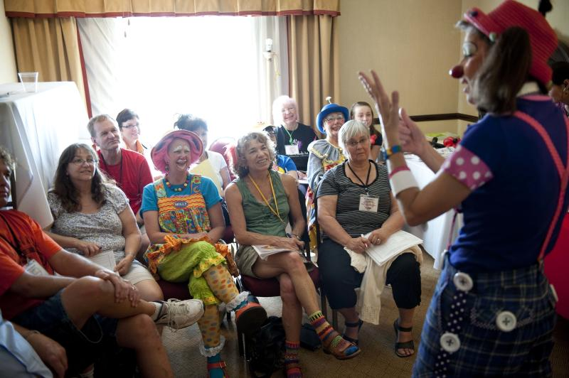 """In a July 31, 2012 photo, Julie Varholdt, or """"Lovely Buttons"""" the clown, teaches a course on how clowns can entertain with everyday objects in a pinch at the third annual Clown Campin' in Ontario, Calif. The week-long event is held for clowns across the United States and Canada to learn, get inspired, and network. (AP Photo/Grant Hindsley)"""