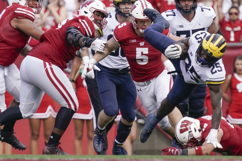 Michigan's Hassan Haskins is tripped up during the second half of an NCAA college football game Saturday, Oct. 2, 2021, in Madison, Wis. (AP Photo/Morry Gash)