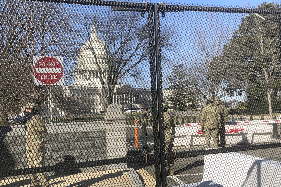Members of the National Guard stand inside anti-scaling fencing that surrounds the Capitol, Sunday, Jan. 10, 2021, in Washington. (AP Photo/Alan Fram)
