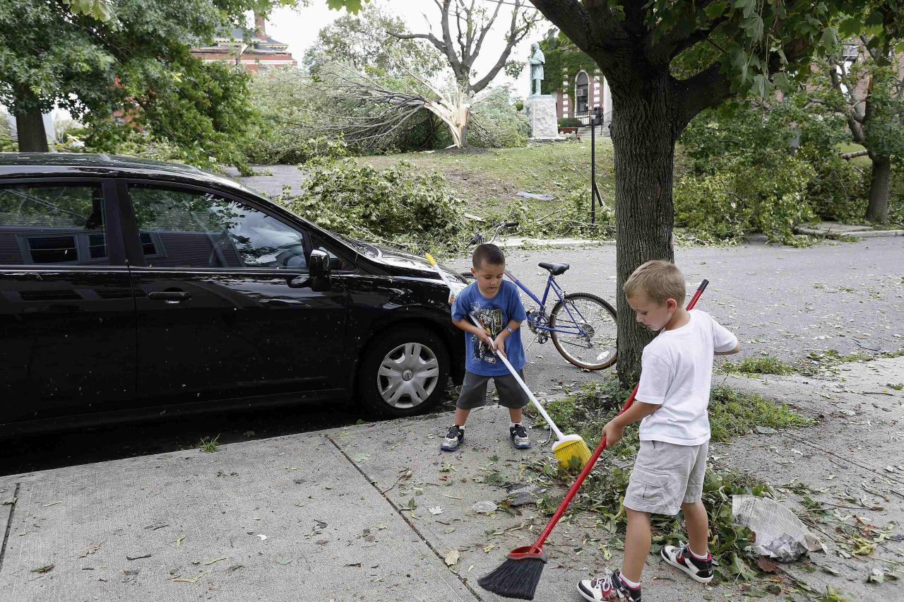 Two boys sweep storm debris from the sidewalk on Cheever Street in Revere, Massachusetts, July 28, 2014. Police and emergency crews in Revere, outside Boston scrambled to clean up after a rare tornado touched down on Monday, downing power lines, damaging homes and overturning at least one car. The National Weather Service confirmed that a tornado touched down during a storm that brought heavy rains, lightning and flooding to Boston and many of its northern suburbs. State emergency management officials said they were not aware of major injuries or fatalities from the storm. REUTERS/Dominick Reuter (UNITED STATES - Tags: ENVIRONMENT DISASTER SOCIETY)