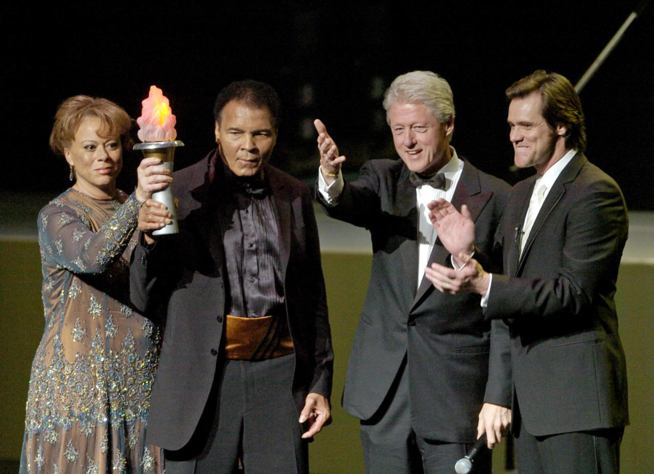 Boxing great Muhammad Ali (2nd L), his wife Lonnie Ali (L), former U.s. president Bill Clinton (2nd R) and actor Jim Carrey wave at the end of the grand opening gala celebration of the Muhammad Ali Center at the Kentucky Center for the Arts in Louisville, Kentucky November 19, 2005. (REUTERS/John Sommers II)