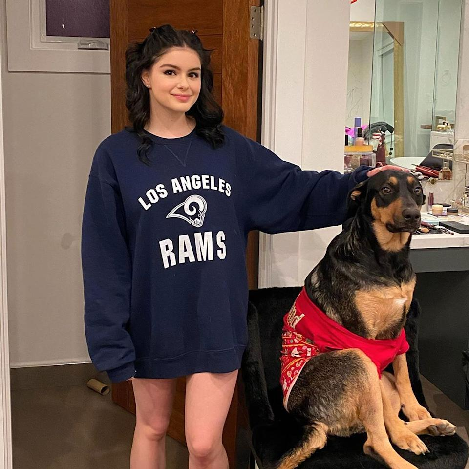 Ariel Winter poses in a sweatshirt with her dog