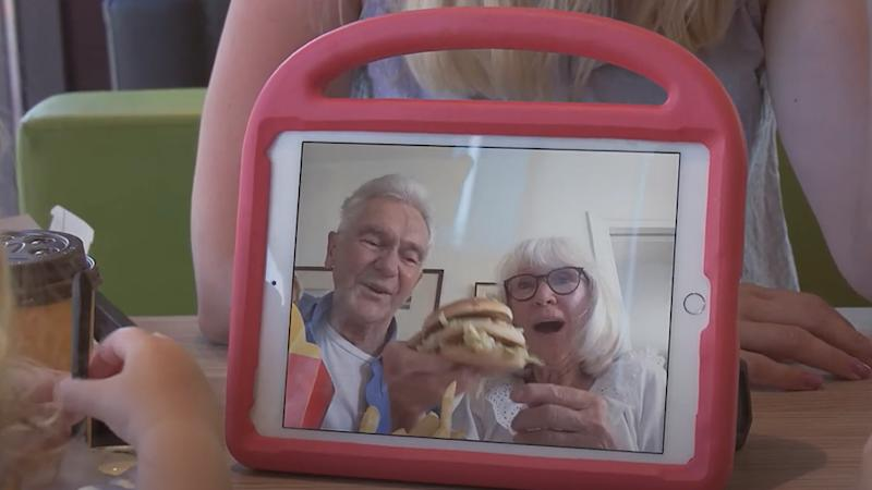 Grandparents sharing a happy meal with their grandchildren over a video chat.