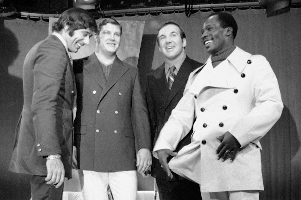 FILE - In this Dec. 8, 1969, file photo, from left, New York Jets' Joe Namath, Bill Mathis, Pete Lammons and Emerson Boozer model Cardin Resort clothes during a New York City taping of the Joe Namath TV show. Bill Mathis, a versatile running back and an original member of the Jets franchise, has died. He was 81. The team announced Mathis' death Tuesday, on Wednesday night, Oct. 21, 2020. (AP Photo/Harry Harris, File)