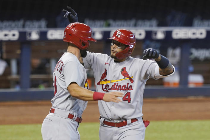 St. Louis Cardinals designated hitter Matt Carpenter (13) congratulates Yadier Molina (4) after Molina hit a home run in the seventh inning of a baseball game against the Miami Marlins, Wednesday, April 7, 2021, in Miami. (AP Photo/Marta Lavandier)