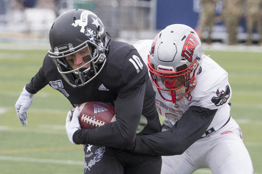 Nevada wide receiver Ben Putman (10) is grabbed by UNLV linebacker Javin White (16) in the first half of an NCAA college football game in Reno, Nev., Saturday, Nov. 30, 2019. (AP Photo/Tom R. Smedes)