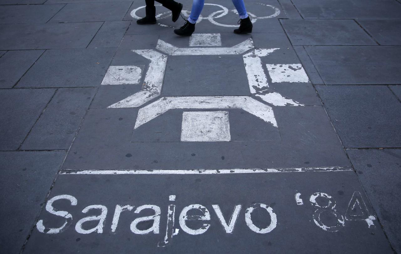 REFILE CORRECTING TYPO IN SARAJEVO   People walk past the logo of the Winter Olympics in Sarajevo, painted on the streets in central Sarajevo October 27, 2013. Abandoned and left to crumble into oblivion, most of the 1984 Winter Olympic venues in Bosnia's capital Sarajevo have been reduced to rubble by neglect as much as the 1990s conflict that tore apart the former Yugoslavia. The bobsleigh and luge track at Mount Trebevic, the Mount Igman ski jumping course and accompanying objects are now decomposing into obscurity. The bobsleigh and luge track, which was also used for World Cup competitions after the Olympics, became a Bosnian-Serb artillery stronghold during the war and is nowadays a target of frequent vandalism. The clock is now ticking towards the 2014 Winter Olympics, with October 29 marking 100 days to the opening of the Games in the Russian city of Sochi. Picture taken on October 27, 2013. REUTERS/Dado Ruvic (BOSNIA AND HERZEGOVINA - Tags: SOCIETY SPORT OLYMPICS SKIING BUSINESS LOGO)  ATTENTION EDITORS: PICTURE 23 OF 23 FOR PACKAGE 'SARAJEVO'S WINTER OLYMPIC LEGACY'. TO FIND ALL IMAGES SEARCH 'DADO IGMAN'