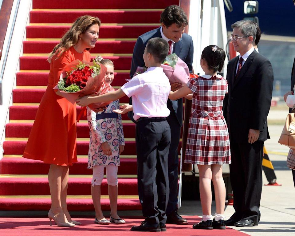 Now: Prime Minister Justin Trudeau, back right, his wife Sophie Gregoire Trudeau, left, and daughter Ella-Grace, back centre, are greeted as they arrive in Beijing, China, on Aug. 30, 2016. THE CANADIAN PRESS/Adrian Wyld