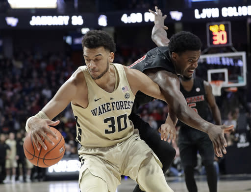 Wake Forest's Olivier Sarr (30) grabs a loose ball in front of North Carolina State's DJ Funderburk (0) during the second half of an NCAA college basketball game in Winston-Salem, N.C., Tuesday, Jan. 15, 2019. (AP Photo/Chuck Burton)