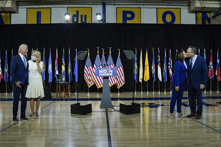 Presumptive Democratic presidential nominee Joe Biden, with wife Dr. Jill Biden, and his running mate Sen. Kamala Harris (D-CA), with husband Douglas Emhoff, stand socially distanced apart after delivering remarks at the Alexis Dupont High School on August 12, 2020 in Wilmington, Delaware.