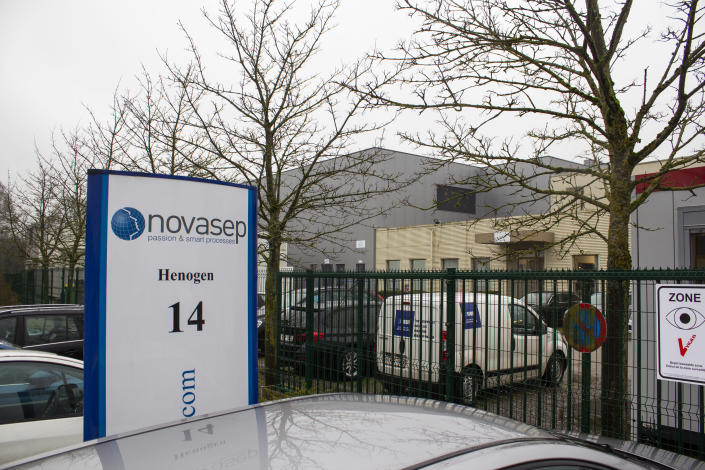 Cars are parked at the entrance of Novasep factory in Seneffe, Belgium, Thursday, Jan. 28, 2021. Belgian health authorities said Thursday they have inspected a pharmaceutical factory located in Belgium to find out whether the expected delays in the deliveries of AstraZeneca's coronavirus vaccines are due to production issues. The Novasep factory in the town of Seneffe is part of the European production chain for AstraZeneca's coronavirus vaccine. (AP Photo/Mark Carlson)