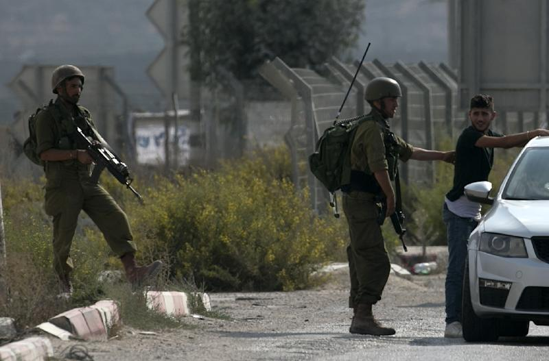 Israeli soldiers carry out searches after an army reservist was stabbed and wounded at the Hawara checkpoint south of the West Bank city of Nablus