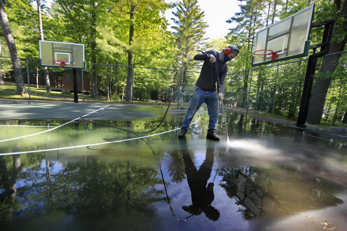 In this Thursday, June 4, 2020 photo, trip leader Gordon Anderson power washes an outdoor basketball court at the Camp Winnebago summer camp in Fayette, Maine. The boys camp is going ahead with plans to open with a reduction in the number of campers and other changes to comply with guidelines for helping prevent the spread of the coronavirus. Many of the nation's 15,000-plus summer camps opting to close because of health concerns surrounding the pandemic, or because of delays in receiving rules or guidelines from licensing officials. (AP Photo/Robert F. Bukaty)
