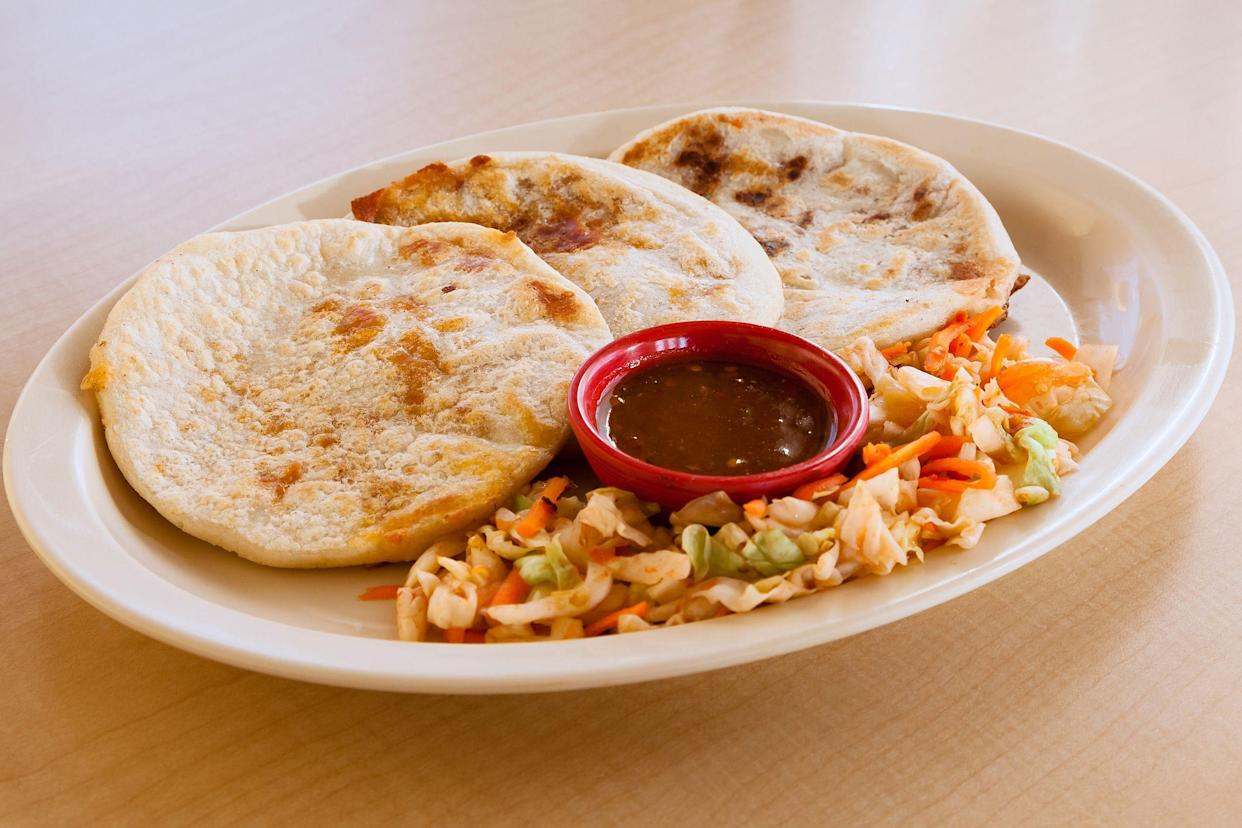 pupusas on plate with slaw and red sauce