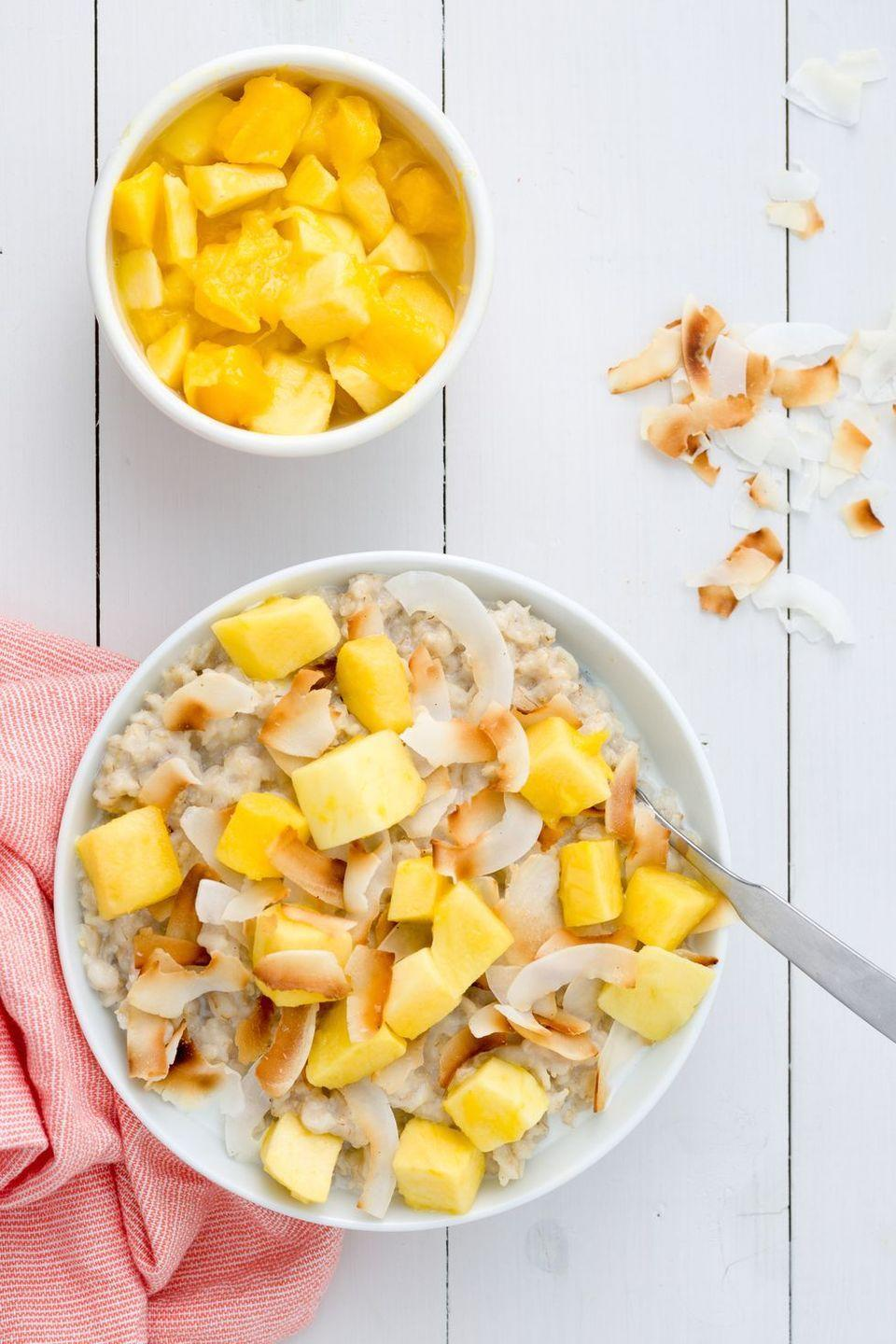 """<p>Cooking the porridge in coconut milk gives this bowl a subtly sweet flavour and extra-creamy texture. Topped with mango and toasted coconut flakes, each bite gets you one step closer to the Tropics.</p><p>Get the <a href=""""https://www.delish.com/uk/cooking/recipes/a29016864/tropical-oatmeal-recipe/"""" rel=""""nofollow noopener"""" target=""""_blank"""" data-ylk=""""slk:Tropical Porridge"""" class=""""link rapid-noclick-resp"""">Tropical Porridge</a> recipe.</p>"""