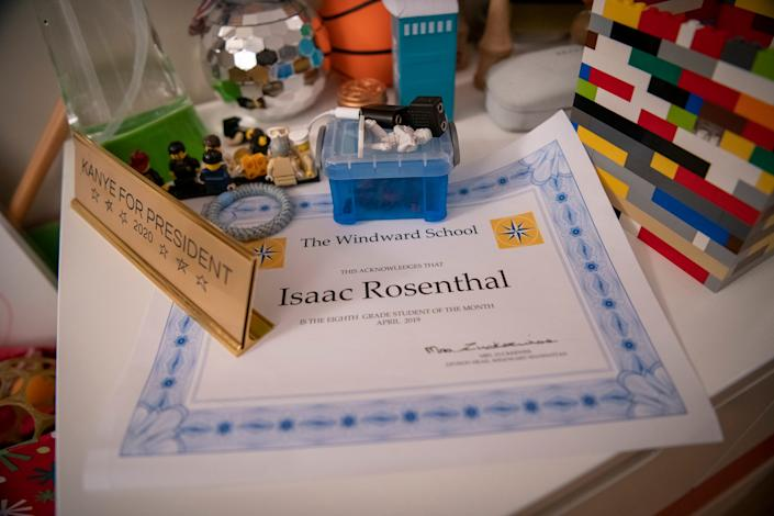 """Isaac Rosenthal's award for 8th grade student of the month from April 2019 sits on the dresser in his bedroom among toys and a plaque that reads """"Kanye for president 2020,"""" which he says he got before Kanye West became a Republican."""