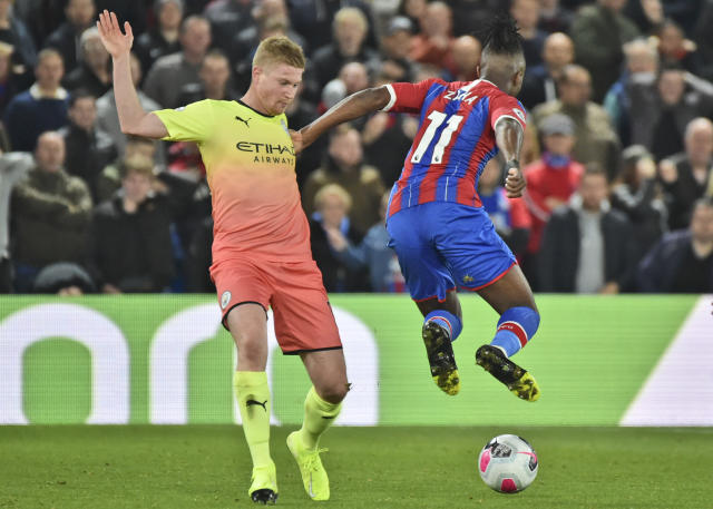 Crystal Palace's Wilfried Zaha, right, jumps as Manchester City's Kevin De Bruyne tackles him during the English Premier League soccer match between Crystal Palace and Manchester City at Selhurst Park in London, England, Saturday, Oct. 19, 2019. (AP Photo/Rui Vieira)
