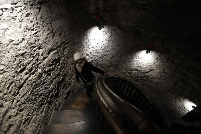 In this picture taken on Tuesday, Nov. 12, 2019, a visitor walks up the stairs of a church tower downtown Prague, Czech Republic. The tower was used for spying on people and western diplomats by the communist secret police. The Czech Republic is marking the 30th anniversary of the 1989 anti-communist Velvet Revolution by looking back at the surreal repression of a nation and resistance against it. (AP Photo/Petr David Josek)