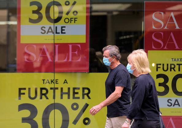 People wearing masks walk past sales sign at Pitt Street Mall in Sydney.