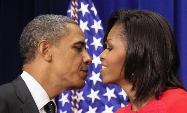 Barack Obama reaches out to kiss first lady Michelle after she introduced him to speak at a bill signing ceremony promoting jobs for veterans at the White House in Washington November 21, 2011.