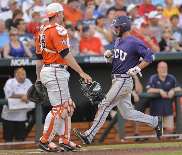 TCU's Garrett Crain, right, crosses home plate with Virginia catcher Nate Irving (18) looking on, left, on a single by TCUs Dylan Fitzgerald, in the second inning of an NCAA baseball College World Series game in Omaha, Neb., Tuesday, June 17, 2014. (AP Photo/Ted Kirk)