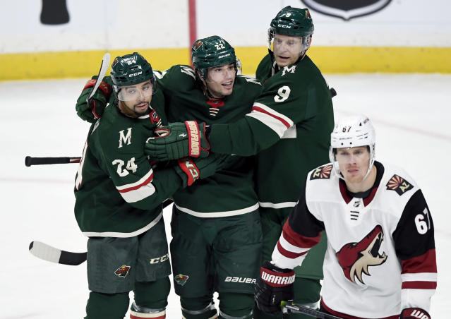 Minnesota Wild's Matt Dumba (24) and Mikko Koivu (9), of Finland, congratulate Kevin Fiala (22), of Switzerland, on his goal as Arizona Coyotes' Lawson Crouse (67) skates to the bench during the first period of an NHL hockey game Thursday, Nov. 14, 2019, in St. Paul, Minn. (AP Photo/Hannah Foslien)