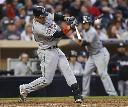 Miami Marlins' Omar Infante drives a high pitch to center field for a sacrifice fly that brings in an insurance run against the San Diego Padres during the eighth inning of a baseball game Saturday, May 5, 2012 in San Diego. (AP Photo/Lenny Ignelzi)