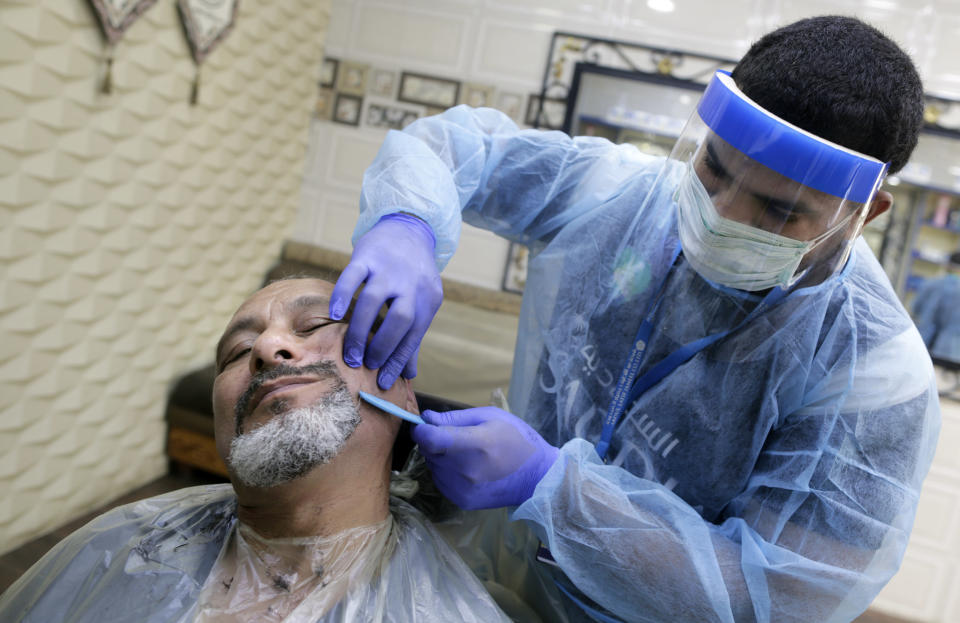 A barber wears a protective face shield and gloves to help curb the spread of the coronavirus, as he shaves the beard of a customer at a local barber shop in Jiddah, Saudi Arabia, Sunday, June 28, 2020. (AP Photo/Amr Nabil)
