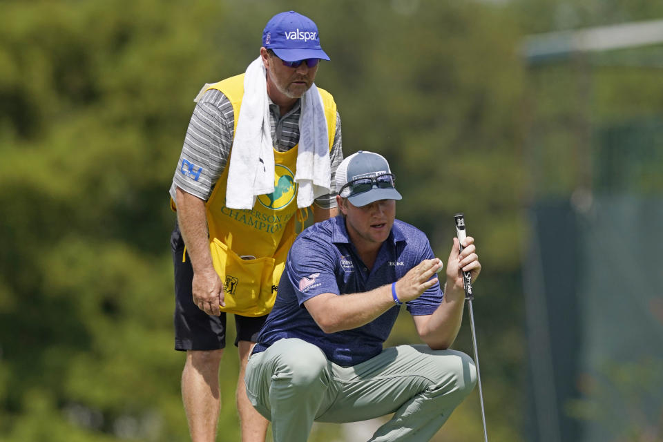 Trey Mullinax, right, discusses his putting strategy with his caddie on the first green during the final round of the Sanderson Farms Championship golf tournament in Jackson, Miss., Sunday, Oct. 3, 2021. (AP Photo/Rogelio V. Solis)