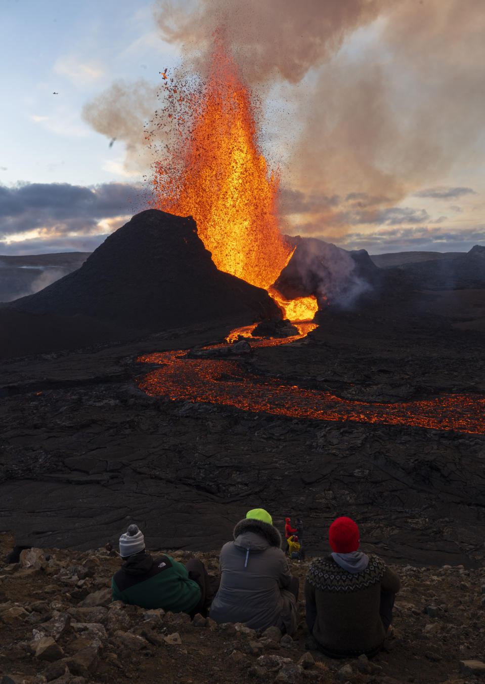 People watch as lava flows from an eruption of the Fagradalsfjall volcano on the Reykjanes Peninsula in southwestern Iceland on Tuesday, May 11, 2021. The glow from the bubbling hot lava spewing out of the Fagradalsfjall volcano can be seen from the outskirts of Iceland's capital, Reykjavík, which is about 32 kilometers (20 miles) away. (AP Photo/Miguel Morenatti)
